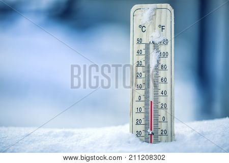 Thermometer On Snow Shows Low Temperatures - Zero. Low Temperatures In Degrees Celsius And Fahrenhei