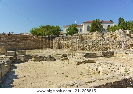 Tourists Visiting The Stage Area Of The Ancient Amphitheatre In Chersonesos Tauride Sunny Day