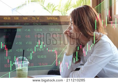 Side view of attractive young Asian business woman thinking and looking through windows with candlestick chart patterns uptrend background. Stock market concept