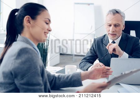 Friendly relations. Selective focus on a bearded chief in formal attire looking at a clipboard with a business document while having a pleasant chat with his up and coming employee.