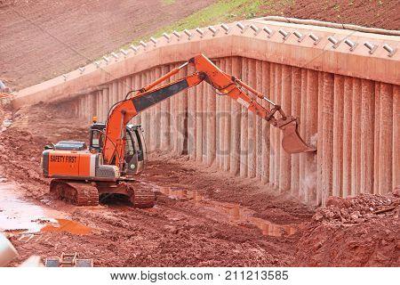 Digger scraping clean concrete bridge support pillars