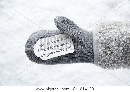 Wool Glove With Label With German Text Wir Wuenschen Ihnen Frohe Weihnachten Und Ein Gutes Neues Jahr Means We Wis You A Merry Christmas And A Happy New Year. White Snow Background.