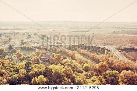 Car driving on road bridge railway colorful trees and fields in sunrays. Seasonal scene. European landscape. Yellow photo filter.