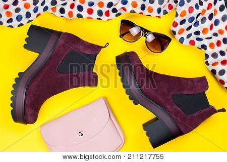 Stylish purple suede ankle boots, pink purse, sunglasses and printed scarf on a bright background