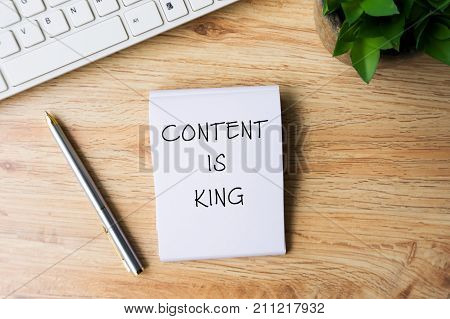 Content Is King Word Written On Notepad With Pen, Computer Keyboard And Flower On Top Of Wooden Tabl