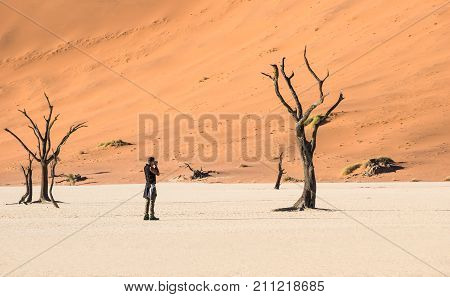 Lonely adventure travel photographer at Deadvlei crater in Sossusvlei territory - Namibian world famous desert - Wander concept with african nature wonder with unique wild landscape in Namibia
