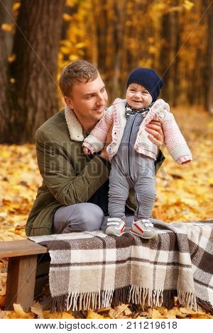young father with a little daughter in autumn park. Happy family, paternal love, autumn season, outdoors concept