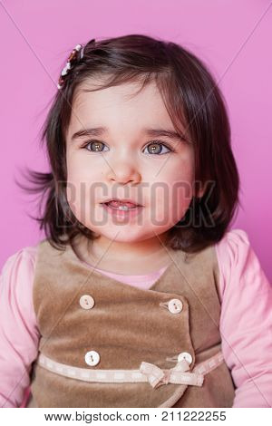 Cute, pretty and happy baby girl toddler smiling portrait, showing two cute teeth in the bottom. 18 or eighteen months old