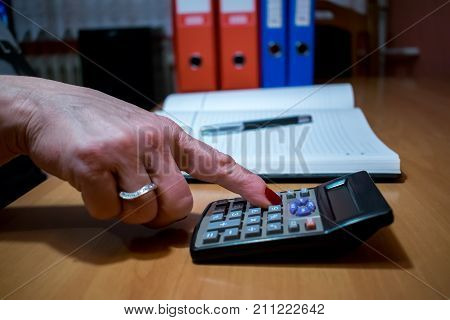 finances economy technology and people concept - close up of woman hands with calculator counting and taking notes to notebook