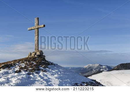 wooden cross on top of a mountain covered with snow in Transylvania
