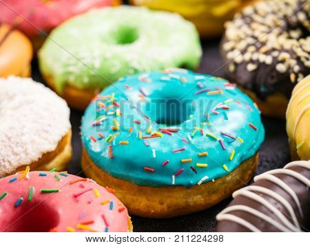 Close up view of assorted colorful donuts on dark background. Focus on blue glazed doughnut with sprinkles. Shallow DOF,