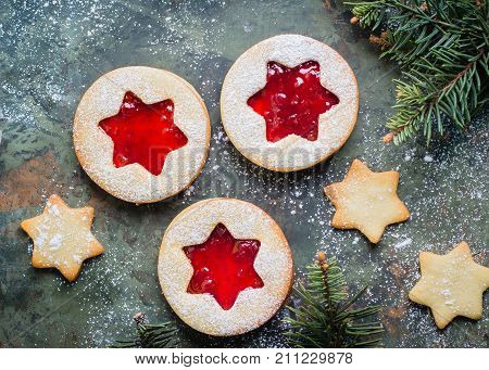 Christmas cookies. Linzer cookies with raspberry jam on green table background. Traditional Austrian biscuits filled. Top view and copy space
