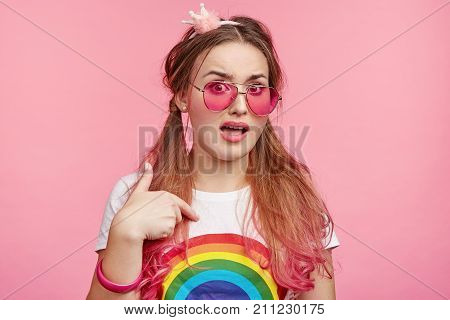 Confused Pin Up Girl With Long Hair Tied In Pony Tails, Wears Pink Spectacles, Points At Herself, Ha