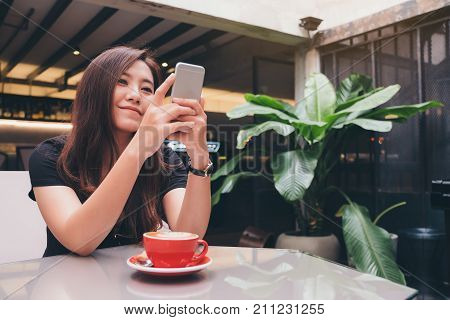 Closeup image of a beautiful Asian woman holding and using smart phone with a red coffee cup on glass table in modern cafe