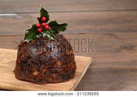 christmas pudding with holly on a wood cutting board