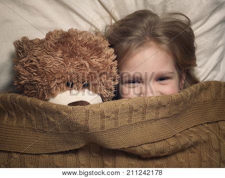 Child and toy bear under blanket in bed
