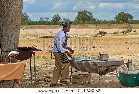 Chef who is preparing breakfast in the African bush for guests to enjoy after having an early morning game drive Hwange National Park Zimbabwe 2013