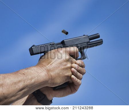 Empty brass flying from a semi auto pistol with sky behind