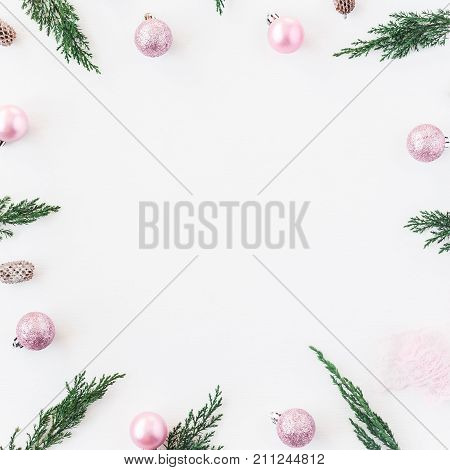 Christmas composition. Christmas frame made of pine branches pink balls pine conces on white background. Flat lay top view copy space square