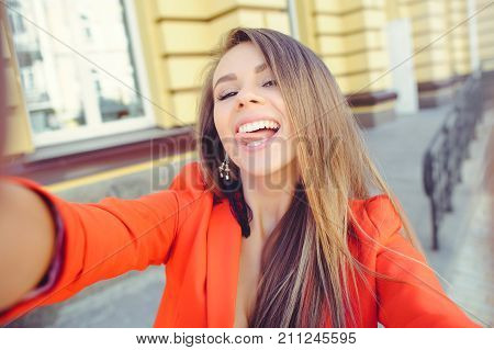 Fashionable Look, Hot Day Model Of A Young Woman Doing Selfie, Wearing A Red Jacket, Blond Hair Outd