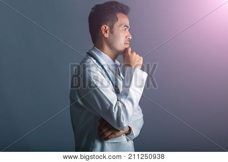 Asian smart doctor standing arms crossed and carrying stethoscope on shoulders at hospital isolated on gray background concept of analysis healthcare and treatment professional.