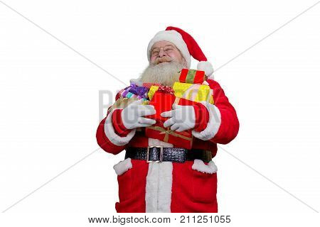 Portrait of Santa Claus with Christmas gifts. Happy Santa Claus holding a pile of gift boxes, isolated on white background. Santa Claus carrying presents to children.