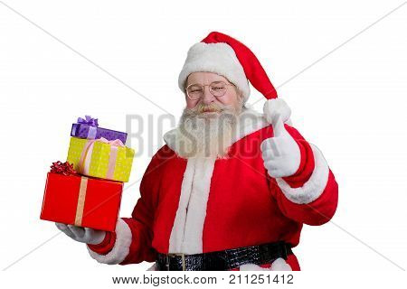 Santa Claus with presents, white background. Portrait of cheerful male Santa Claus with colored gift boxes. Santa Claus with real beard giving thumb up on white background.
