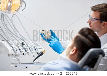 Rearview shot of a professional mature male dentist holding dental mold talking to his patient explaining something copyspace model teeth health treatment communication dentistry medicine.