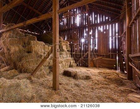 HDR image of an old Barn with the sun streaming from outside and straw and hay on the floor of the hayloft poster