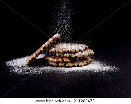 White Plate With Homemade Belgian Waffles, On Top Of Poured Sifting Of Powdered Sugar On Black Backg