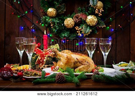 Baked Turkey Or Chicken. The Christmas Table Is Served With A Turkey, Decorated With Bright Tinsel A