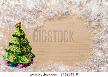 Christmas background. White frosty branches, covered with snow, green decorative glass Christmas tree and copy space on natural uncolored  wooden background.