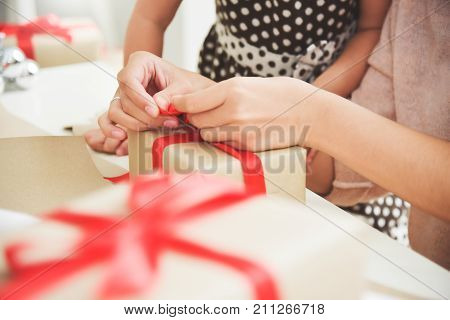 Closeup Young mother and her daughter hands wrapping a brown gift box for Birthday Christmas and New year. Happy Asian family at the house. Copy space.