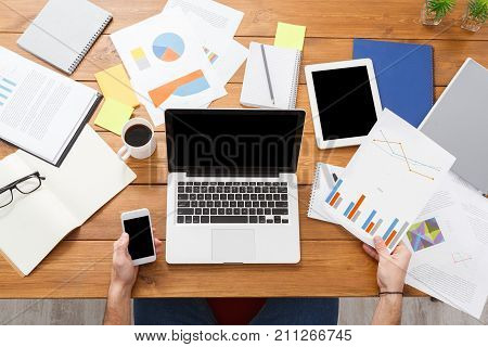 Top view of the businessman using mobile phone and working with laptop by messy desk. Empty screen for copy space, top view. Overworking concept