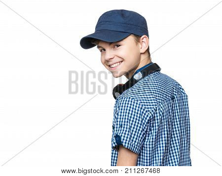 Portrait of young student with cap and headphones, isolated on white background. Teen boy smiling and looking at camera.