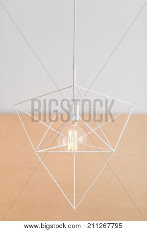 Suspended geometric hexagon chandelier loft style in a modern house interior. Two color background..