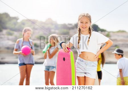Cute confident girl standing in shorts on beach holding body board and her friends on background chatting