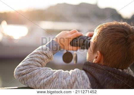 Little caucasian boy watching looking searching gazing by binoculars in sunset