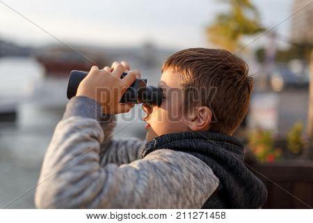 Little caucasian boy watching looking gazing searching for by binoculars
