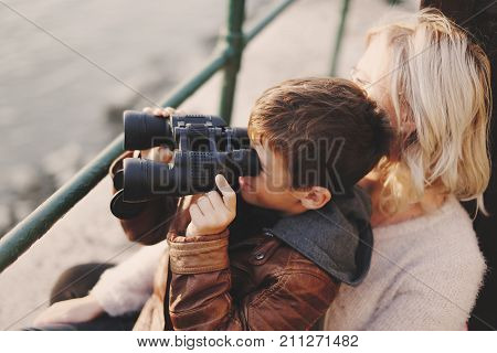 Little caucasian boy with binoculars looking watching gazing searching for at mother