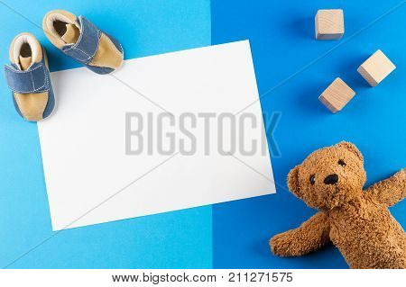 Its a boy, blue theme Baby shower or Nursery background with blank card, teddy besr, wooden blocks and baby shoes on blue background