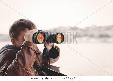 Little caucasian boy watching looking gazing searching for by binoculars during trip