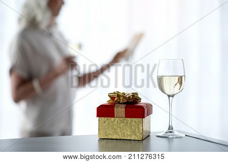 Close up focus on colorful wrapped gift box and glass of champagne on table. Pensive woman is standing near window and looking at photo frame on background
