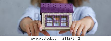 Beautiful woman portrait. Holds a miniature toy doll house toy style mulatto curly hair with white locks eye view of the camera