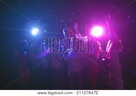 Happy friends at birthday party at night club. Classy people enjoying life, dancing, drinking champagne and having fun at dark smoky background, showered with confetti. B-day celebration background poster