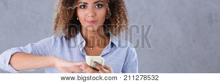 Beautiful woman portrait. Scattering money notes dollars in fashion vows style mulatto curly hair with white locks eye view of the camera