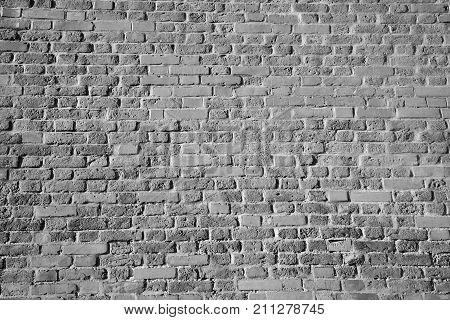 textured high wall, laying bricks b & W