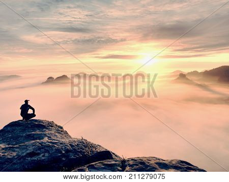 Moment Of Loneliness On Exposed Rocky Summit. Man In Black Enjoy Marvelous View. Hiker Sit On The Pe