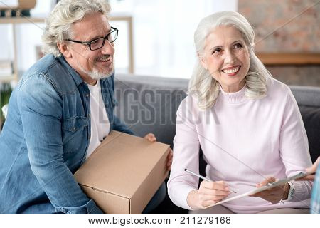 Joyful senior married couple is receiving mail post at home. Woman is sitting on sofa and putting signature on paper. Man is holding cardboard box and smiling