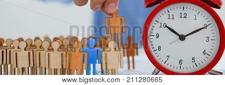 Businessman with his hand puts a miniature silhouette of a man in his rightful place. Red alarm clockwork means a staff schedule for each unit of the work cycle of an enterprise